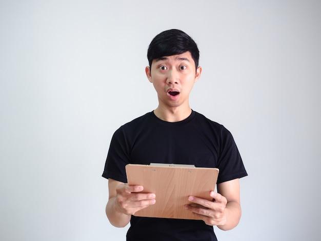 Jovem, camisa preta, rosto chocado segurando uma prancheta de madeira, olhando para a câmera em fundo branco