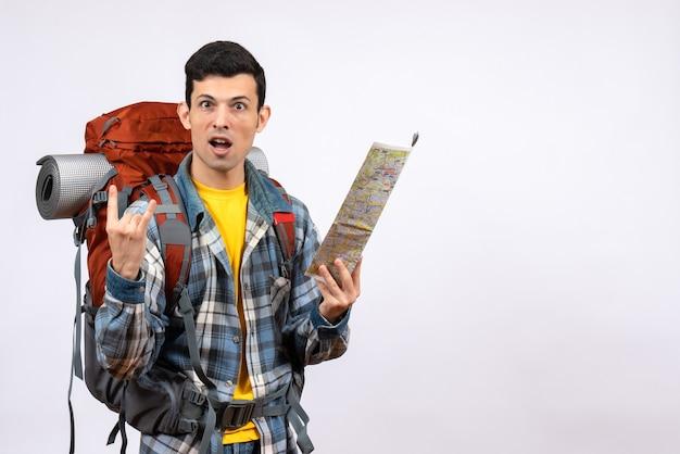 Jovem campista confuso de frente com a mochila segurando o mapa