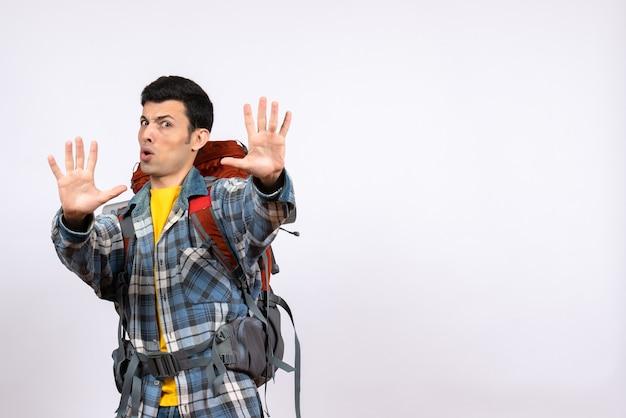 Jovem campista insatisfeito de frente com mochila fazendo sinal de pare