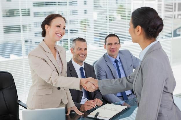 Jovem candidato bonito apertando as mãos com futuros empregadores