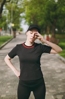 Jovem cansada atlética linda morena de uniforme preto e boné em pé, descansando e mantendo a mão perto da cabeça após a corrida, treinando no parque da cidade ao ar livre