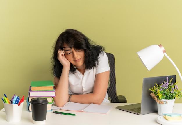 Jovem cansada e bonita caucasiana colegial de óculos sentada na mesa com as ferramentas da escola coloca a mão no rosto dorme isolada no espaço verde com espaço de cópia