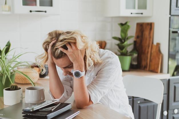 Jovem cansada e chateada com laptop trabalhando em casa na cozinha.