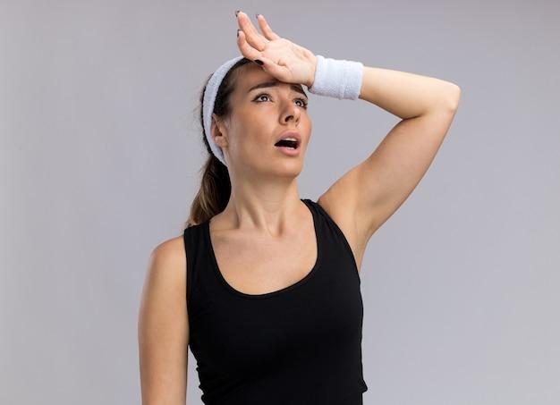 Jovem cansada e muito esportiva usando bandana e pulseiras, olhando para cima, mantendo a mão na testa isolada na parede branca com espaço de cópia