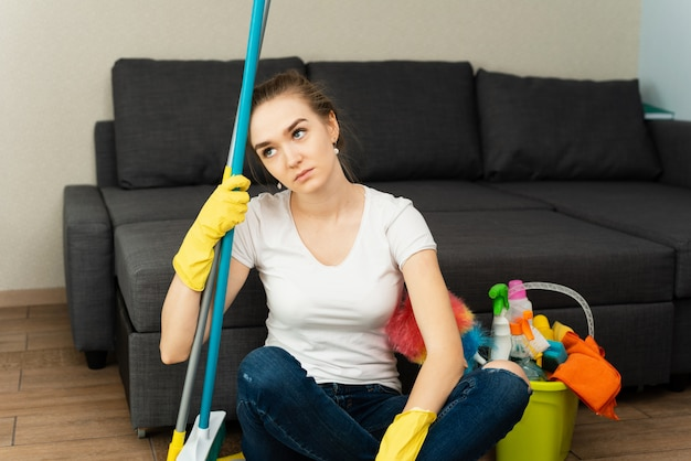 Jovem cansada está sentada no chão com produtos de limpeza