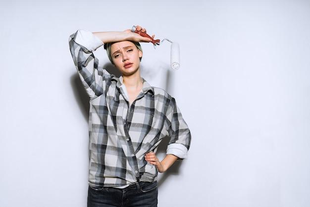 Jovem cansada faz consertos no apartamento, segura um rolo para pintar as paredes, enxuga o suor da testa