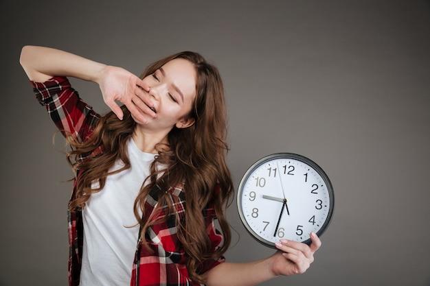 Jovem cansada segurando o relógio e bocejando.