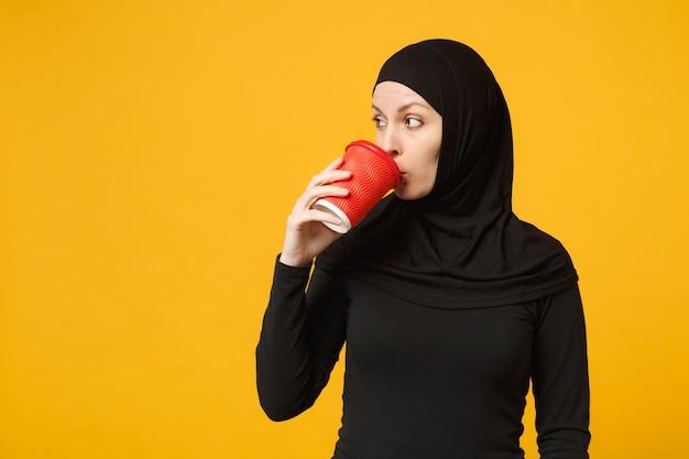 Jovem cansada triste chateada mulher muçulmana árabe em roupas pretas de hijab segurar o copo de papel de café isolado no retrato de parede amarela. conceito de estilo de vida religioso de pessoas.