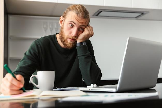 Jovem cansado barbudo sentado na cozinha tomando café usando o computador portátil.