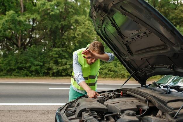 Jovem cansado com o capô aberto corrige o problema com o motor, avaria do carro. automóvel quebrado ou conserto de veículo, problema com automóvel na rodovia