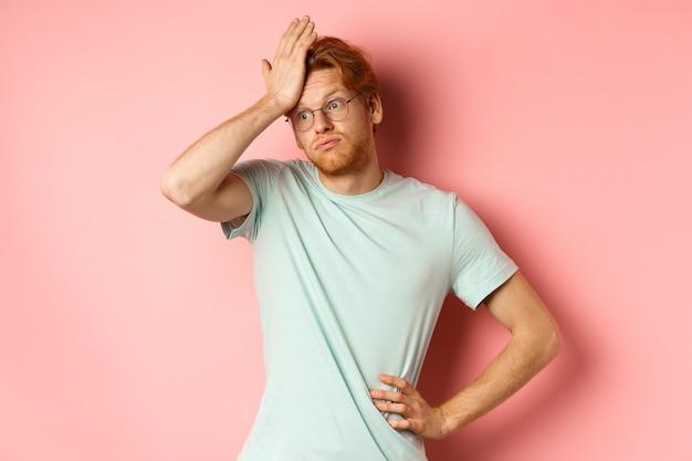 Jovem cansado, de cabelo vermelho, usando óculos, parecendo irritado e tenso, fazendo gesto com a palma da mão e expirar incomodado, em pé sobre um fundo rosa.