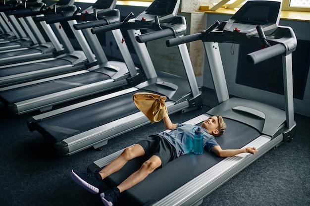 Jovem cansado deitado na esteira na academia, executando a máquina. menino em treinamento, saúde e estilo de vida saudável, estudante em exercício