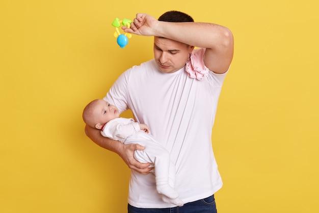 Jovem cansado em uma camiseta branca casual segurando a filha recém-nascida nas mãos