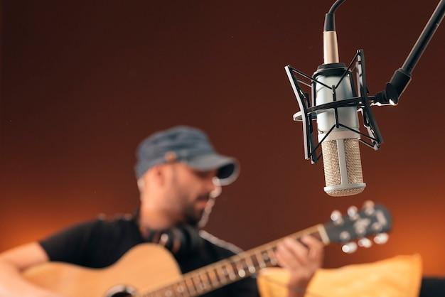 Jovem cantando em direto no estúdio musical.