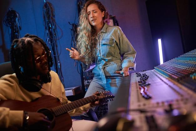 Jovem cantora cantando uma música no estúdio