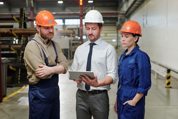 Jovem capataz com capacete e roupa formal fazendo apresentação de novo projeto para sua equipe em reunião de trabalho