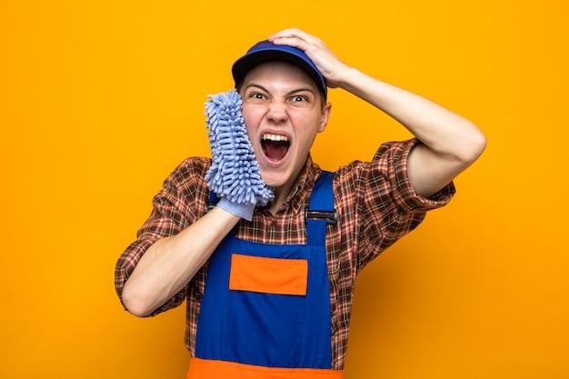 Jovem cara de limpeza empolgado segurando a cabeça usando uniforme e boné segurando um pano no rosto