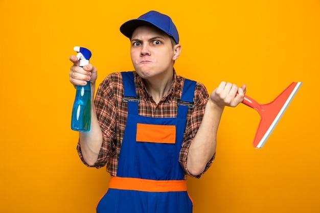 Jovem cara de limpeza preocupado, usando uniforme e boné segurando o agente de limpeza com a cabeça do esfregão