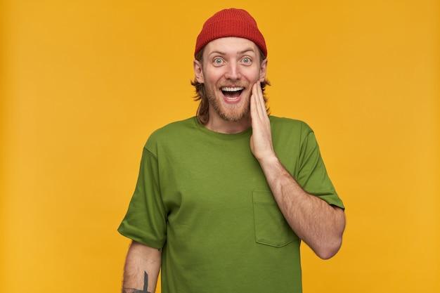 Jovem, cara feliz com cabelo loiro, barba e bigode. vestindo camiseta verde e gorro vermelho. tem tatuagem. tocando sua bochecha. isolado sobre a parede amarela