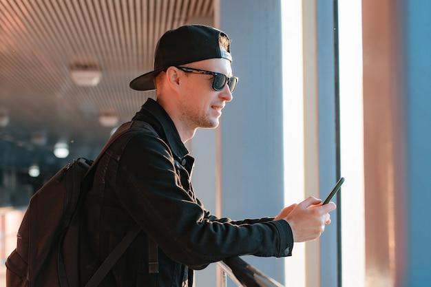 Jovem cara moderno na moda, um homem de boné preto e óculos escuros com um smartphone, fala ao telefone em um meio urbano de cidade em um túnel sob os raios de sol do sol.