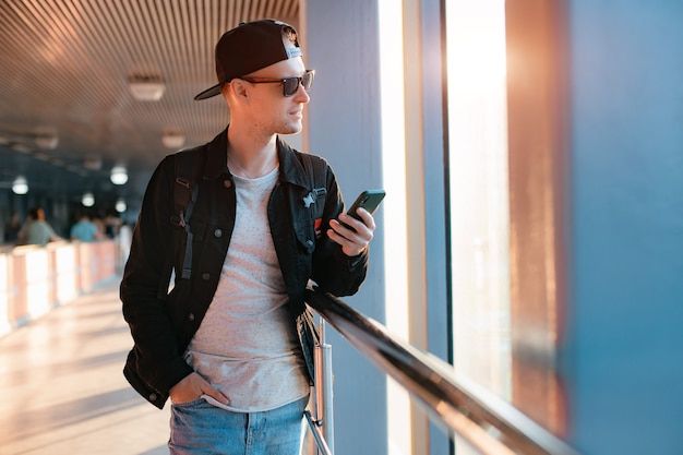 Jovem cara moderno na moda, um homem de boné preto e óculos escuros com um smartphone, fala ao telefone em um meio urbano de cidade em um túnel sob os raios de sol do sol. Foto Premium