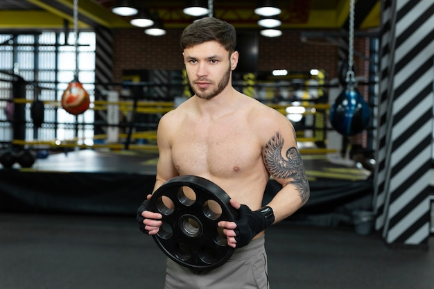 Jovem cara musculoso com um torso nu posando segurando uma panqueca na barra