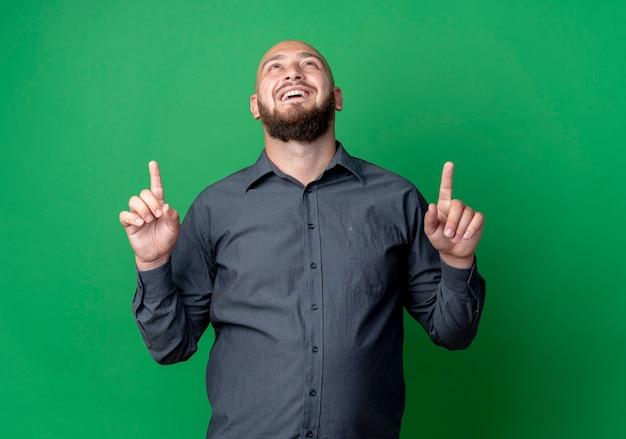 Jovem careca alegre homem de call center olhando e apontando para cima isolado no verde