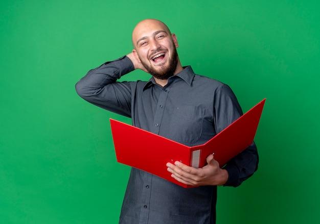 Jovem careca alegre homem de call center segurando uma pasta aberta e colocando a mão atrás da cabeça isolada no verde