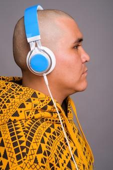Jovem careca asiática ouvindo música contra parede cinza