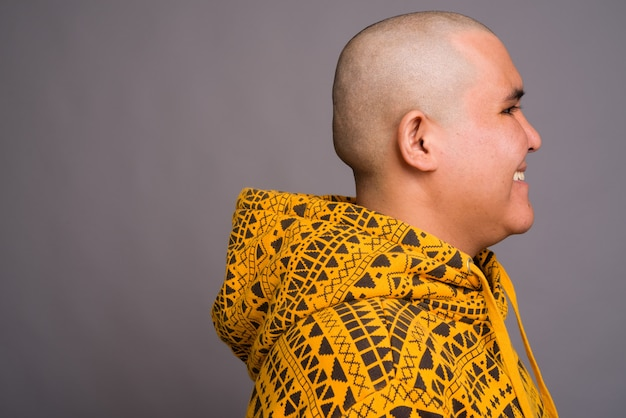 Jovem careca asiático vestindo capuz contra parede cinza