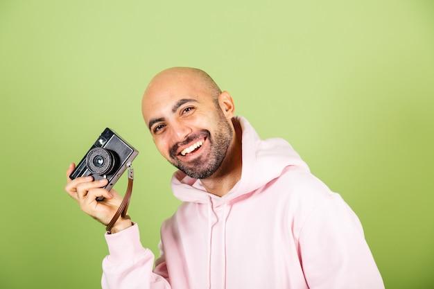 Jovem careca caucasiano com capuz rosa isolado, hipster positivo segurando a câmera