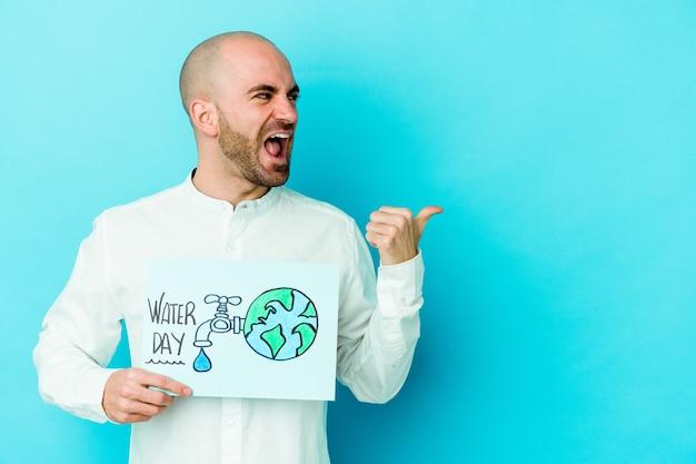 Jovem careca comemorando o dia mundial da água isolado na parede azul apontando com o dedo polegar afastado, rindo e despreocupado