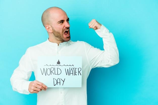 Jovem careca comemorando o dia mundial da água, isolado na parede azul, levantando o punho após a vitória, conceito vencedor