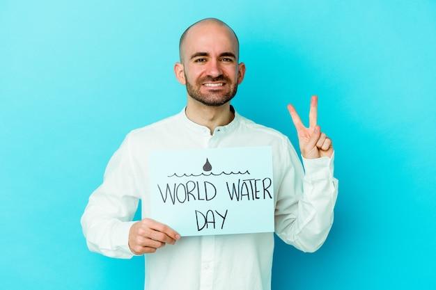 Jovem careca comemorando o dia mundial da água, isolado na parede azul, mostrando o número dois com os dedos