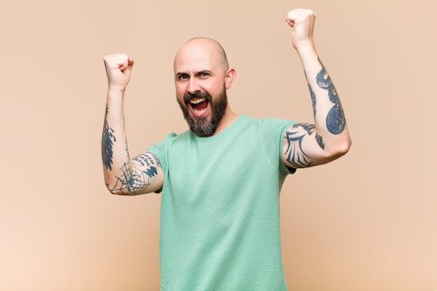 Jovem careca e barbudo gritando triunfantemente, parecendo um vencedor animado, feliz e surpreso, comemorando