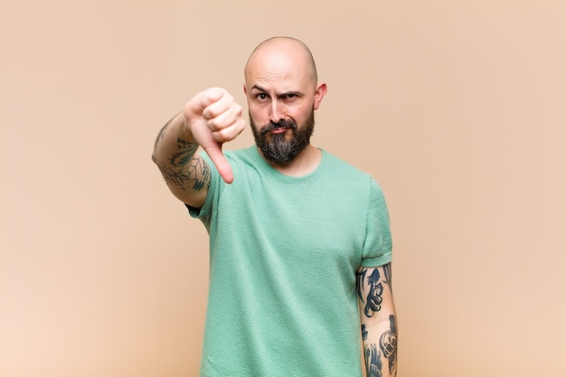 Jovem careca e barbudo sentindo-se zangado, zangado, irritado, desapontado ou descontente, mostrando os polegares para baixo com um olhar sério