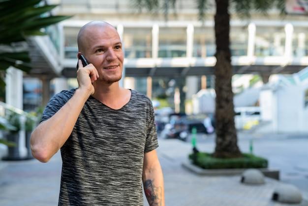 Jovem careca feliz sorrindo enquanto pensa e fala no celular
