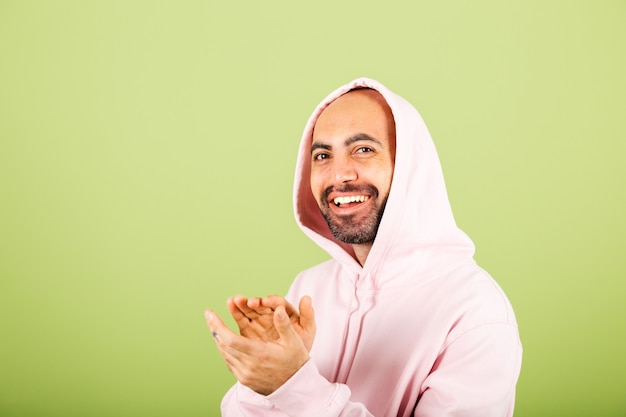 Jovem careca homem caucasiano com capuz rosa isolado, feliz batendo palmas e aplaudindo feliz e alegre, sorrindo orgulhosas mãos juntas