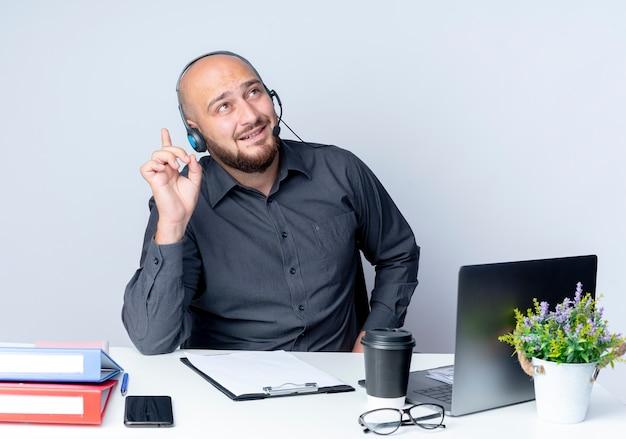 Jovem careca impressionado pelo call center usando fone de ouvido, sentado à mesa com ferramentas de trabalho, olhando e apontando para cima, isolado no branco