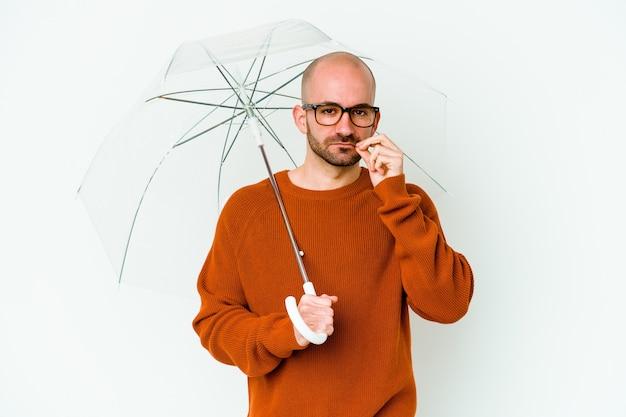 Jovem careca segurando um guarda-chuva isolado com os dedos nos lábios, mantendo um segredo.