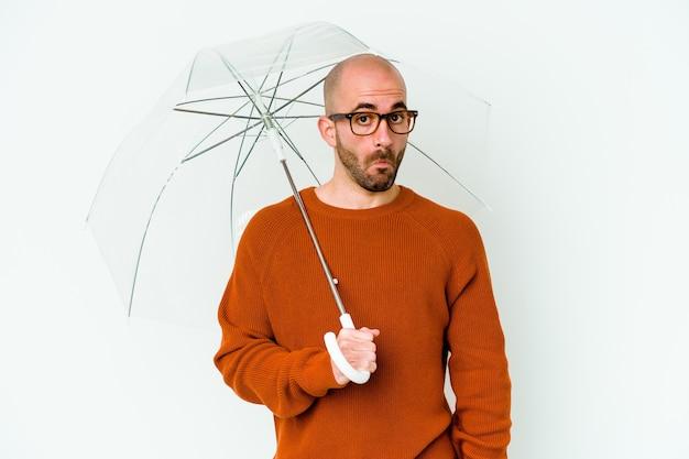 Jovem careca segurando um guarda-chuva isolado encolhe os ombros e abre os olhos confusos.
