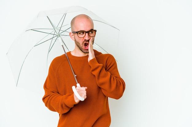 Jovem careca segurando um guarda-chuva isolado está contando uma notícia secreta sobre a travagem e olhando para o lado