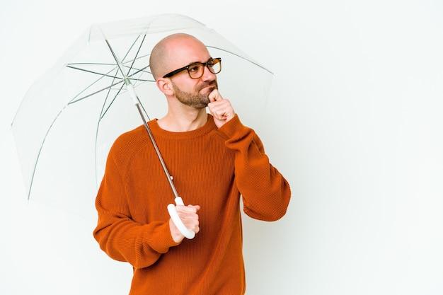 Jovem careca segurando um guarda-chuva isolado, olhando de soslaio com expressão duvidosa e cética.