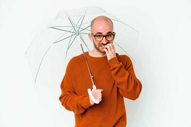 Jovem careca segurando um guarda-chuva isolado unhas roendo, nervoso e muito ansioso.