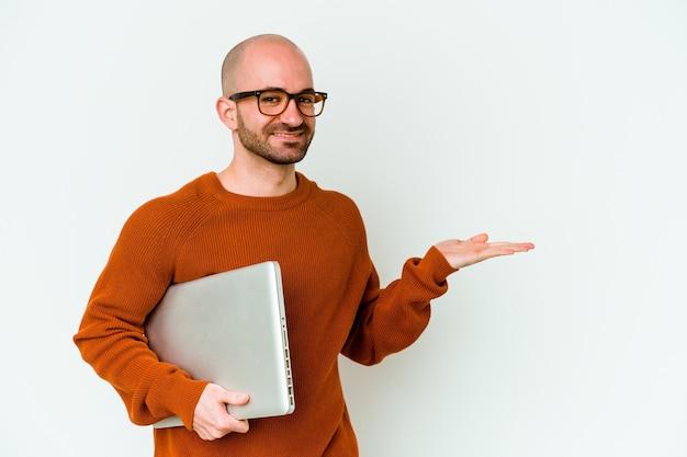Jovem careca segurando um laptop isolado na parede branca, mostrando um espaço de cópia na palma da mão e segurando a outra mão na cintura.