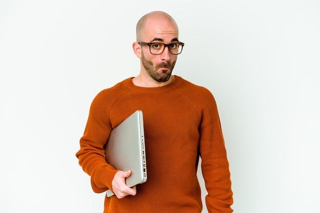 Jovem careca segurando um laptop isolado no fundo branco encolhe os ombros e abre os olhos confusos.