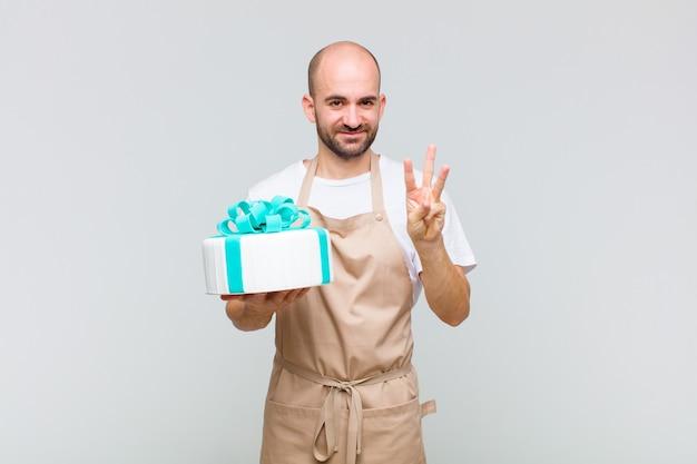 Jovem careca sorrindo e parecendo amigável, mostrando o número três ou o terceiro com a mão para a frente, em contagem regressiva