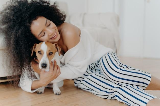 Jovem carinhosa abraça o cão com amor e carinho, mantém os olhos fechados do prazer, sorri gentilmente