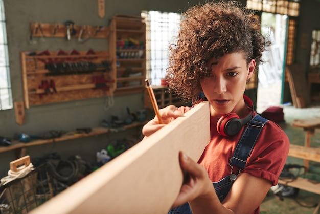 Jovem carpinteira concentrada com cabelo encaracolado, segurando uma prancha de madeira e estimando seu comprimento antes de serrar