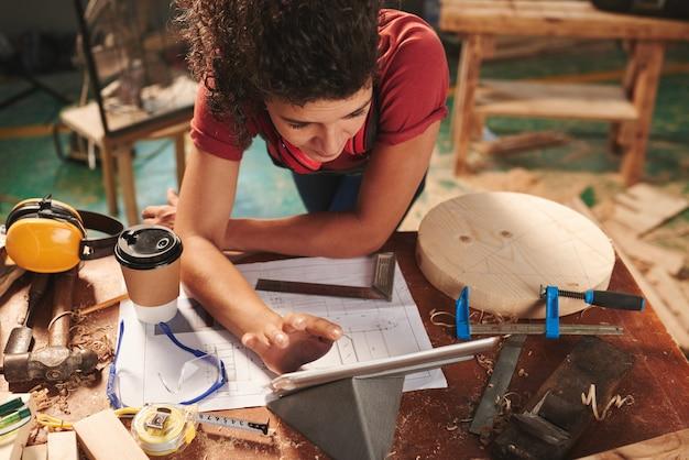 Jovem carpinteira lendo o manual em um tablet digital enquanto se inclina sobre uma mesa coberta com rascunhos, ferramentas e serragem